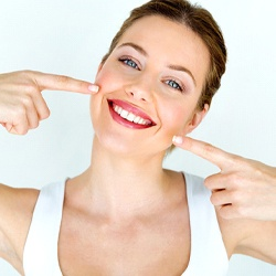 Woman pointing to her smile after direct bonding.