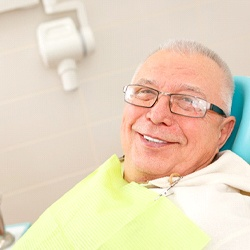 A older man in the dentist chair smiling