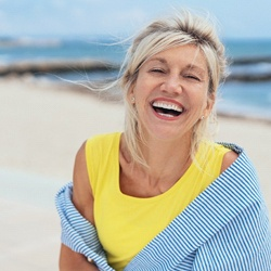 An older woman smiling on the beach