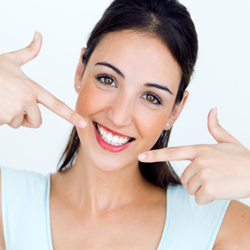 Woman pointing to bright white smile