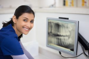 Dental assistant looking at x-ray