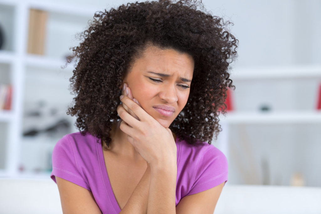 Woman in pain considers visiting an emergency dentist.