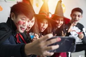 adults dressed up as witches and vampires and taking a picture together